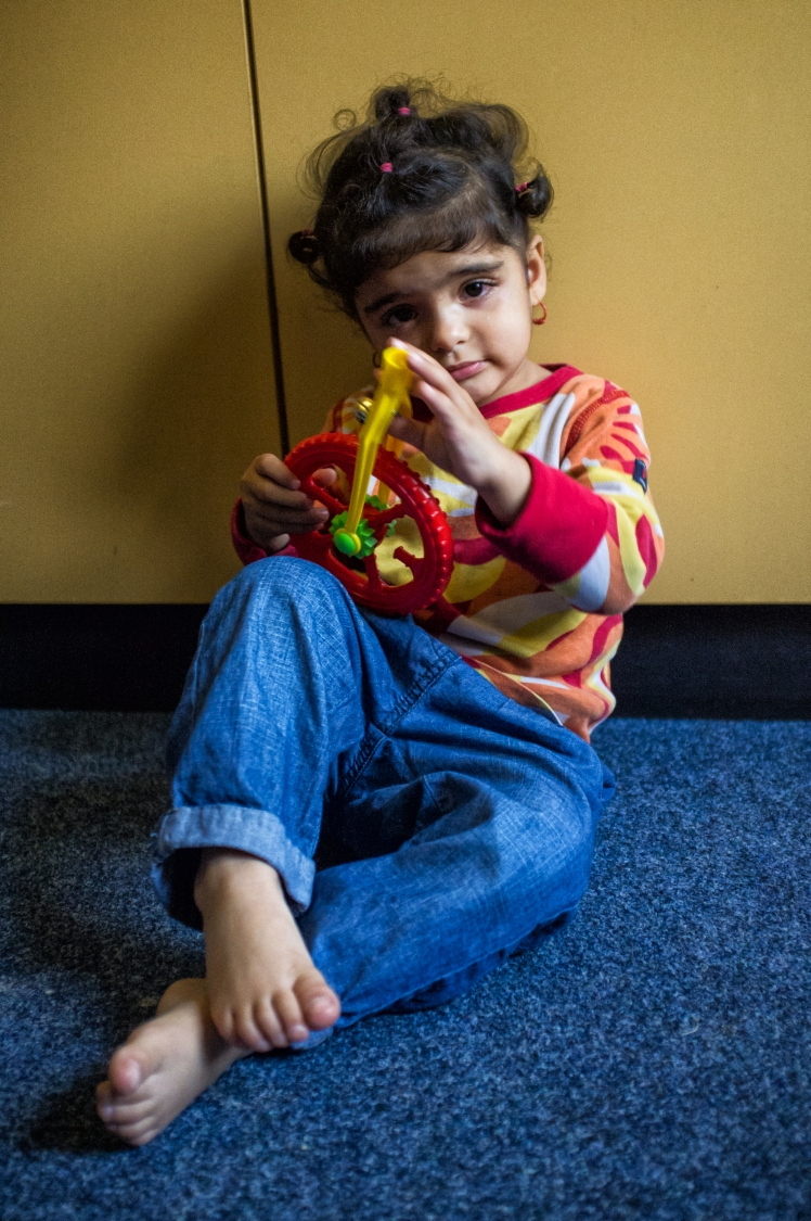 A young girl from Iraq, a refugee, plays with a donated toy