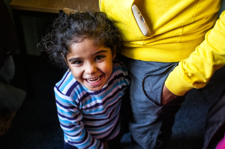 A young girl from Iraq, a refugee, with her father