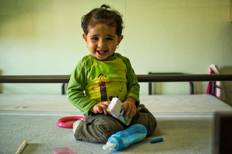 A baby from Iraq, a refugee, sits on a bunkbed in Berlin, Germany