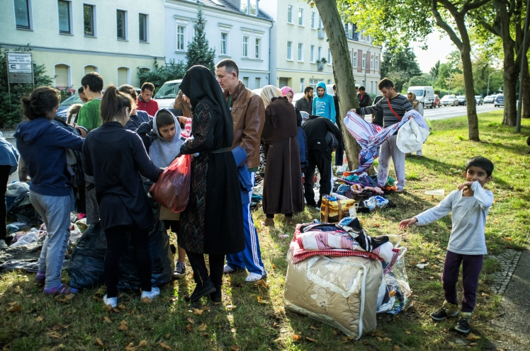Refugees in Berlin, Germany, looking through clothes donated by German volunteers