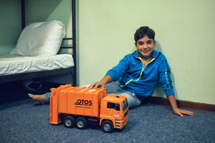 A young Iraqi boy, a refugee, plays with a truck donated by German volunteers